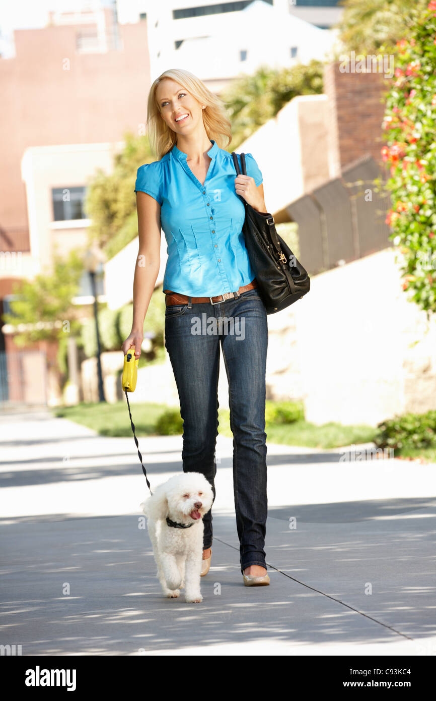 Woman walking with dog in city street - Stock Image