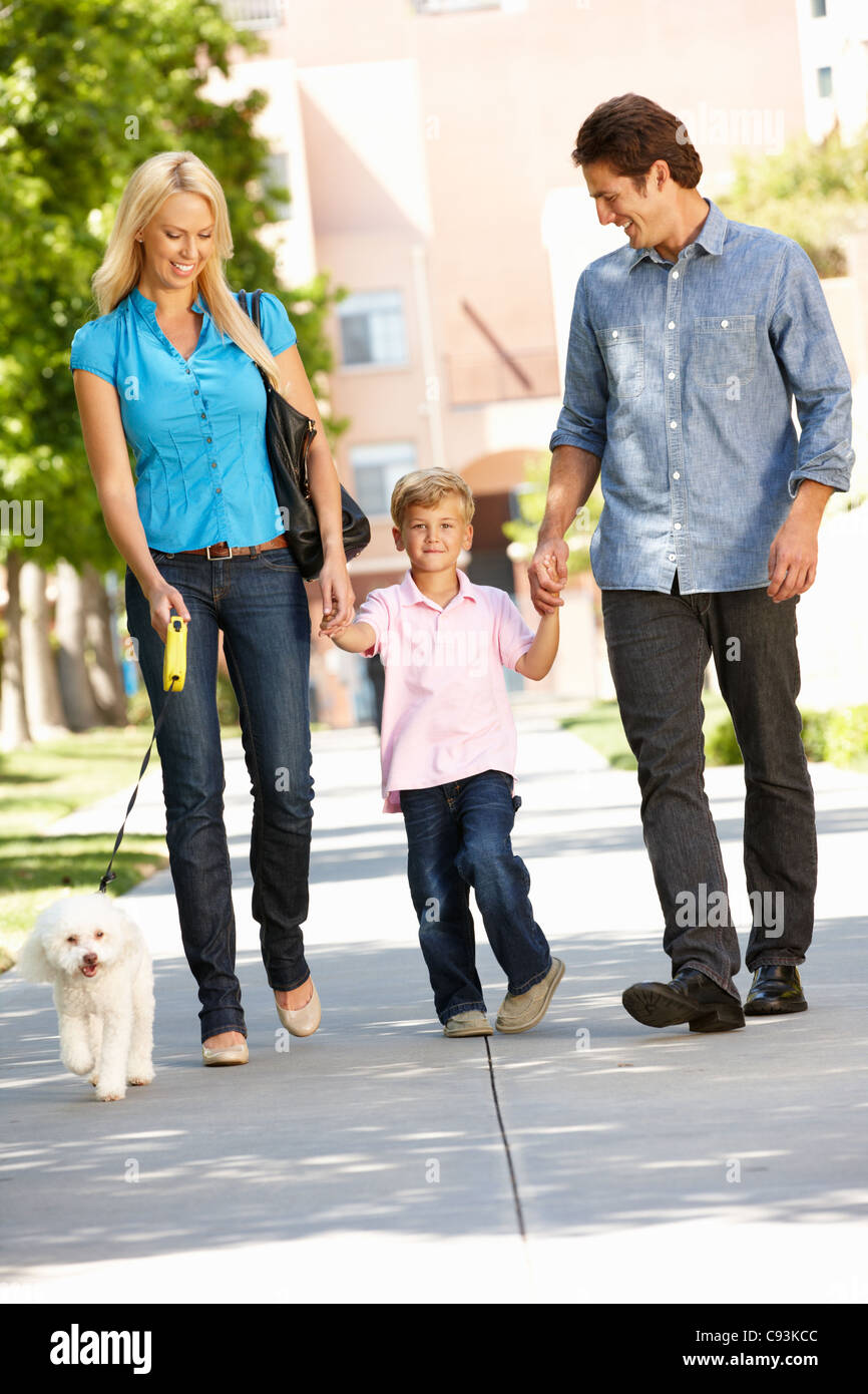 Family walking with dog in city street - Stock Image
