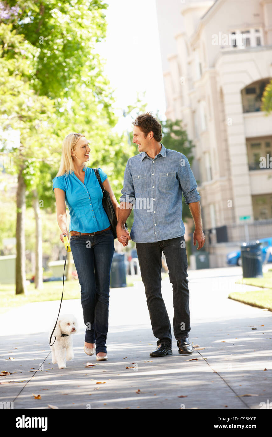 Couple walking with dog in city street - Stock Image