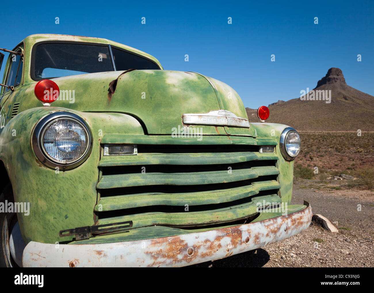 The front of an old, green, rusting and abandoned Chevrolet truck on a sunny day along Route 66, Arizona, USA Stock Photo