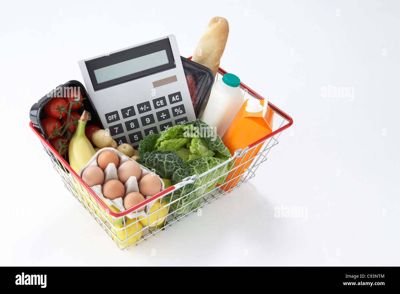 Basket of groceries and calculator - Stock Image