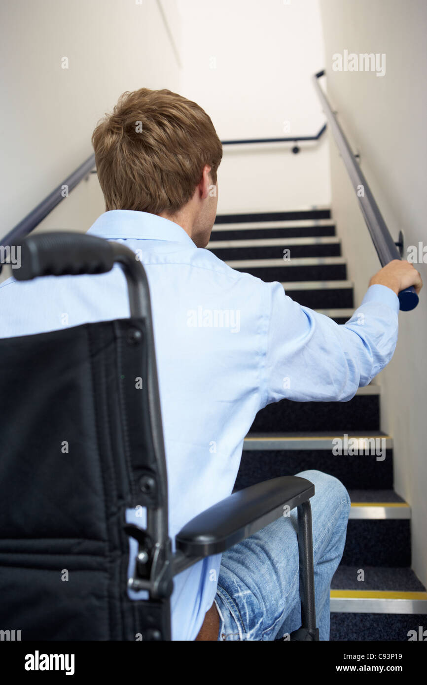 Man in wheelchair at foot of stairs - Stock Image