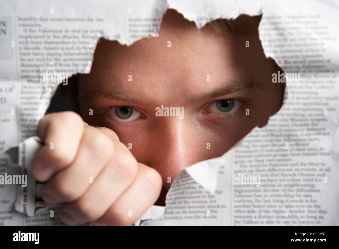 Man looking through hole in newspaper - Stock Image