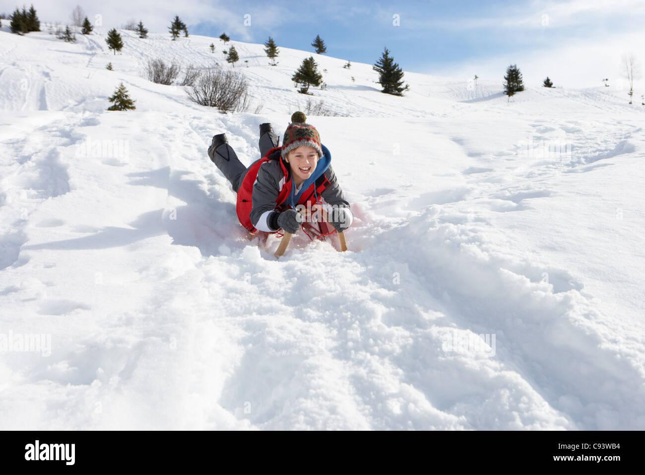 Pre Teen Boy On A Sled In The Snow