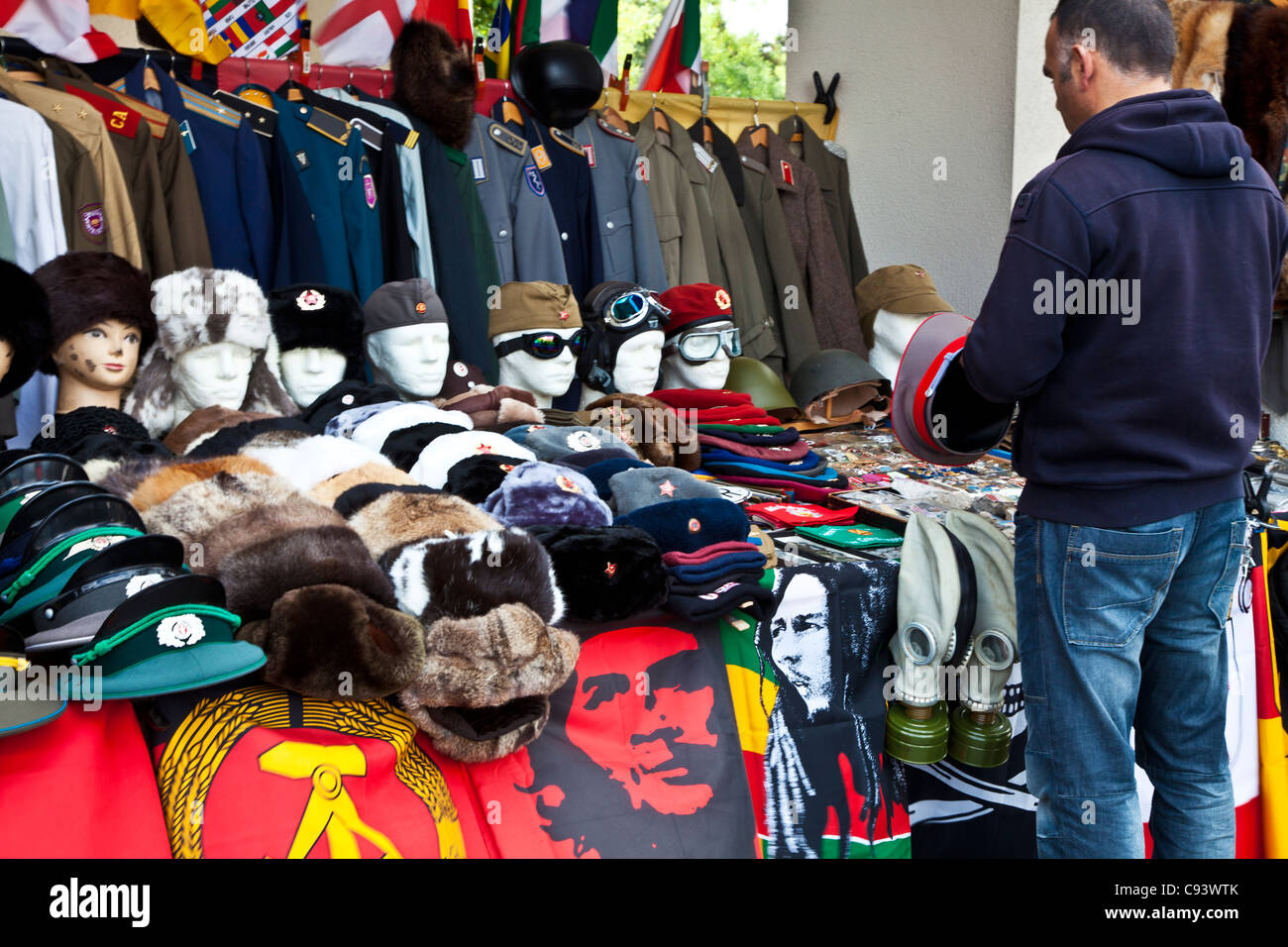 A male tourist inspects a hat and wartime military uniforms and memorabilia on a tourist souvenir stall in Berlin, - Stock Image