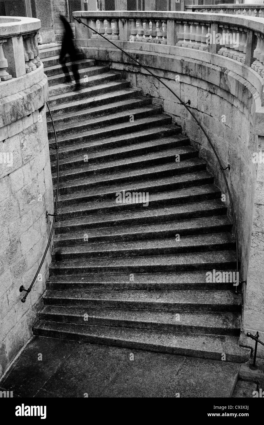 Person climbing curvy stairs - Stock Image
