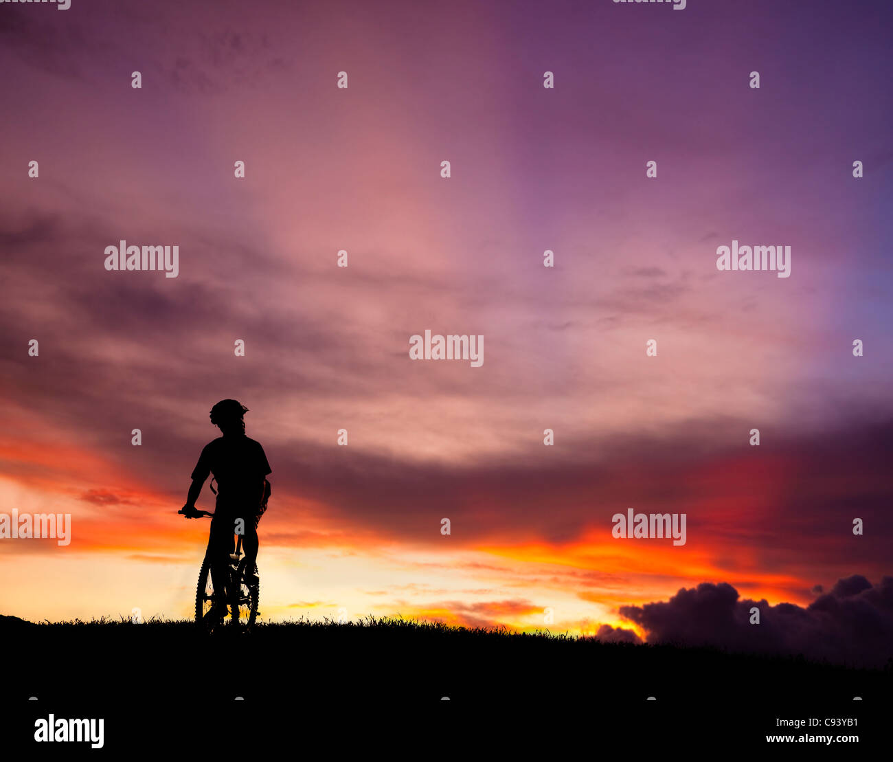 The silhouette of mountain bicycle rider on the hill with beautiful sunrise background - Stock Image
