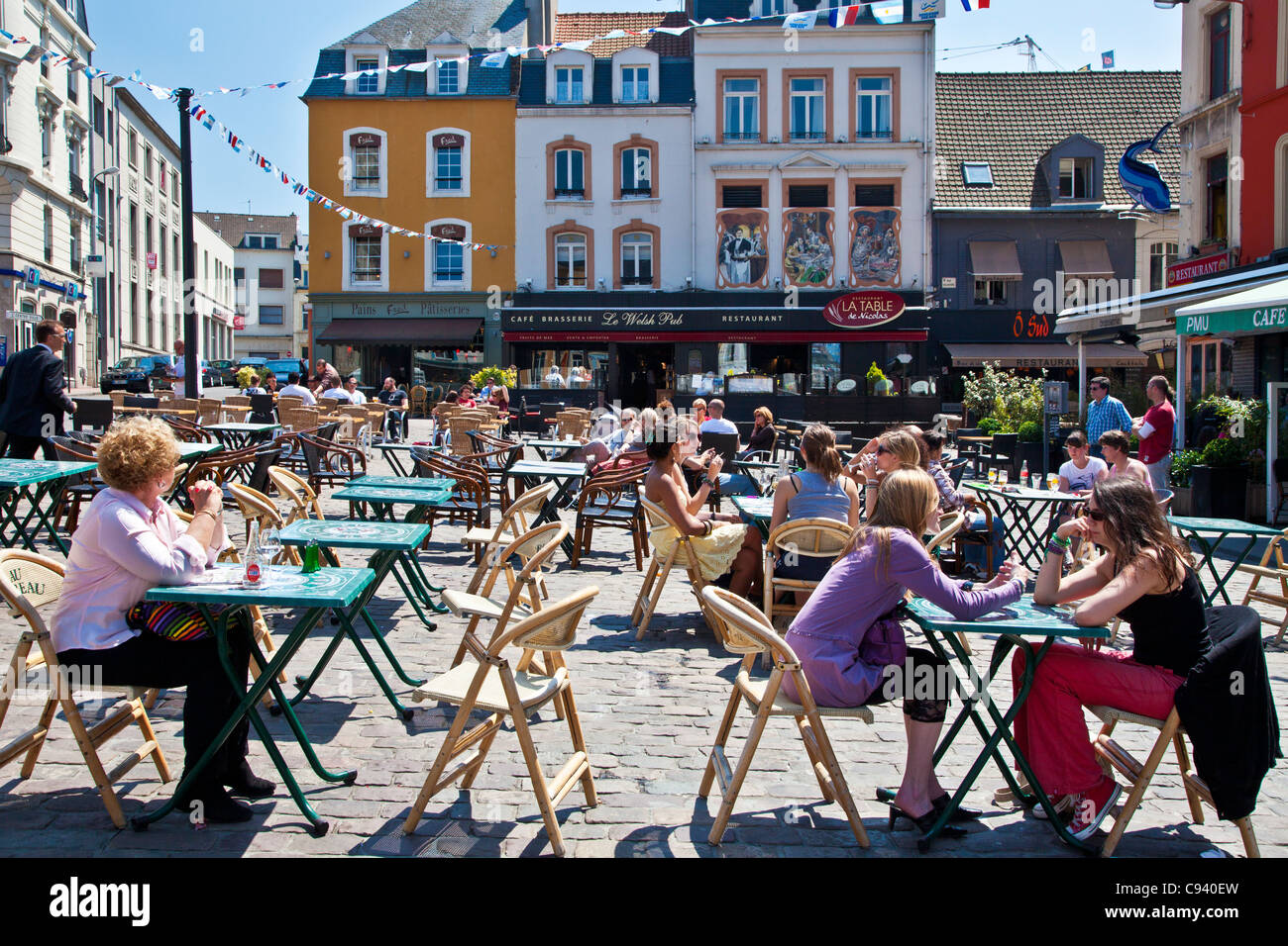People enjoying the sunshine and chatting at outdoor cafes in the Place Dalton in Boulogne, France - Stock Image