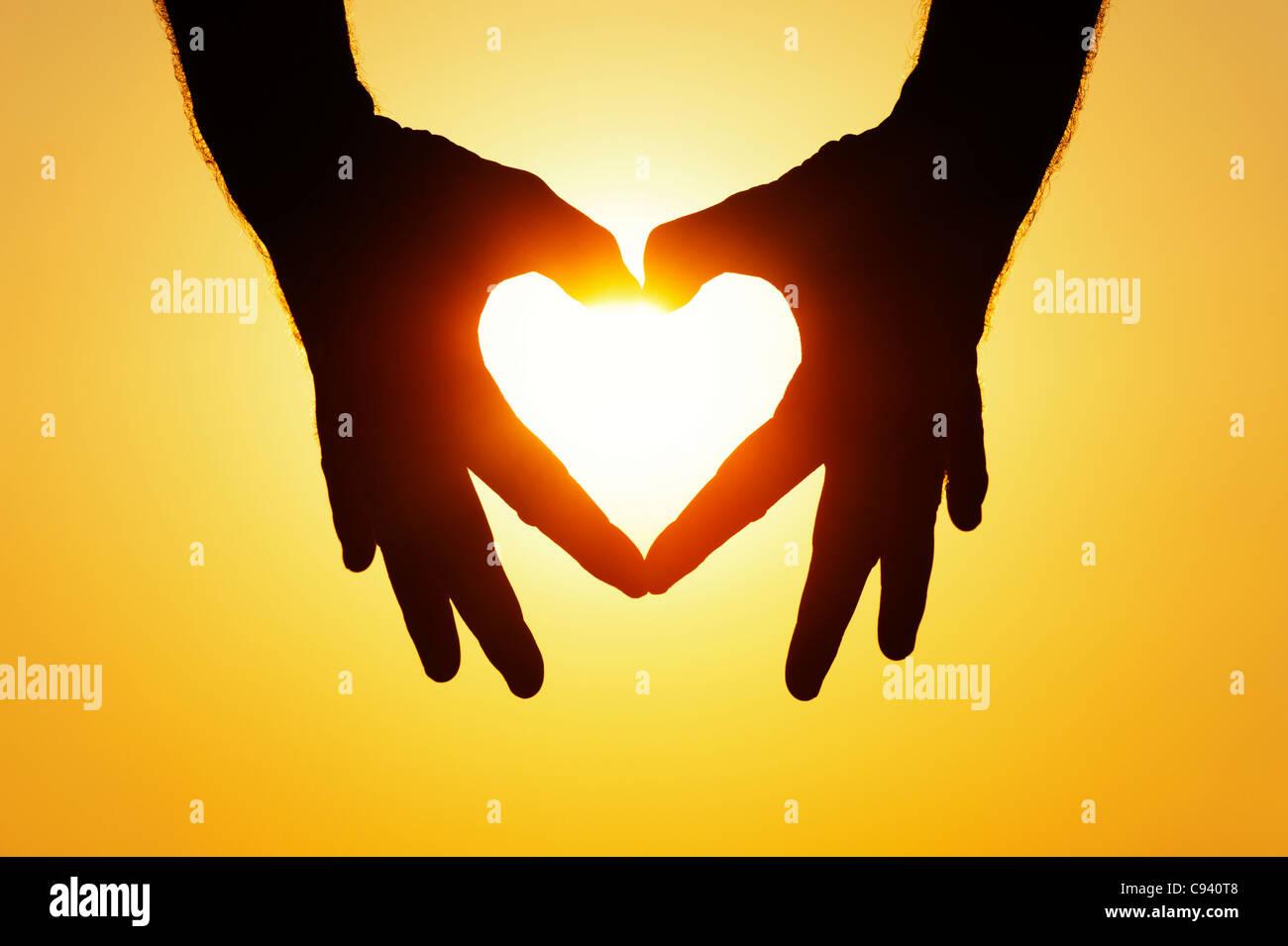 Heart shape hands silhouette against setting sun - Stock Image