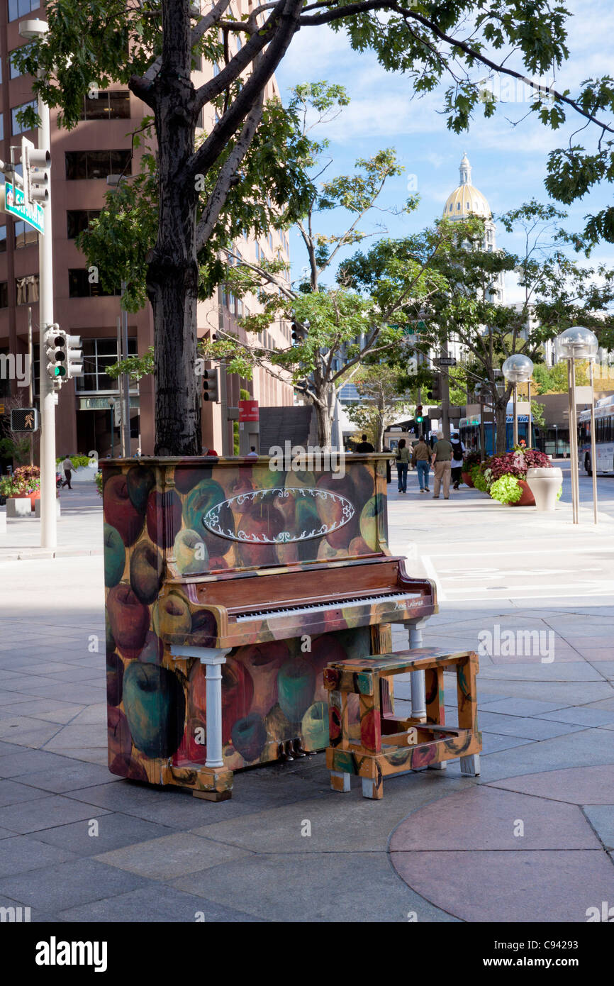 Painted piano on 16th Street Mall in downtown Denver, Colorado, with capitol building dome in background - Stock Image