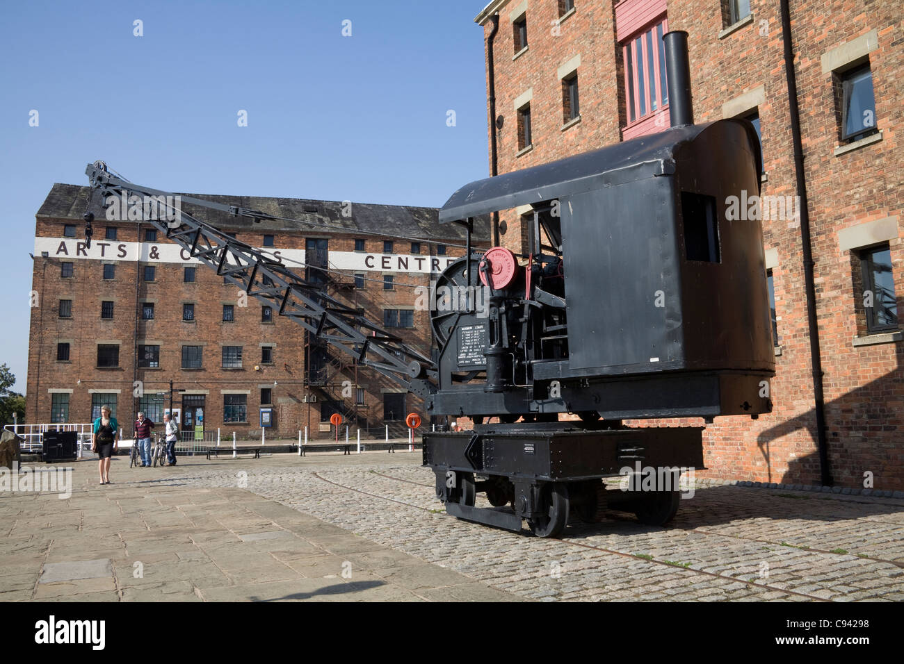 Gloucester England Crane on quayside of renovated Dock Basin with Arts and Crafts Antiques Centre behind Stock Photo
