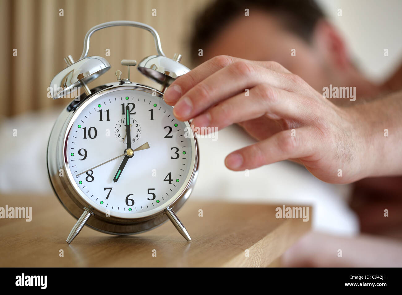 Turning off an alarm clock - Stock Image