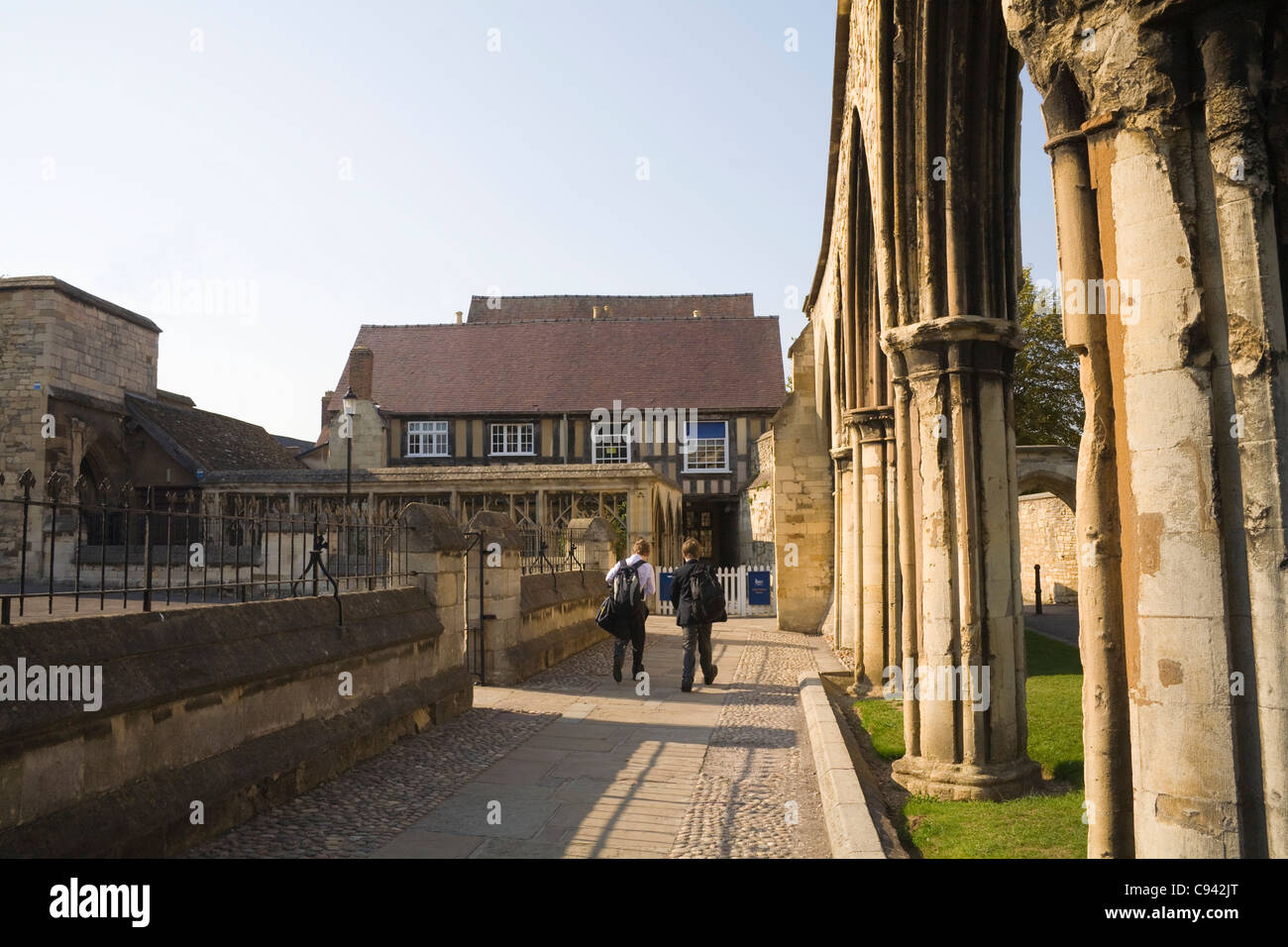 Gloucester England Two Kings School pupils walking past the Infirmary Arches to medieval building - Stock Image