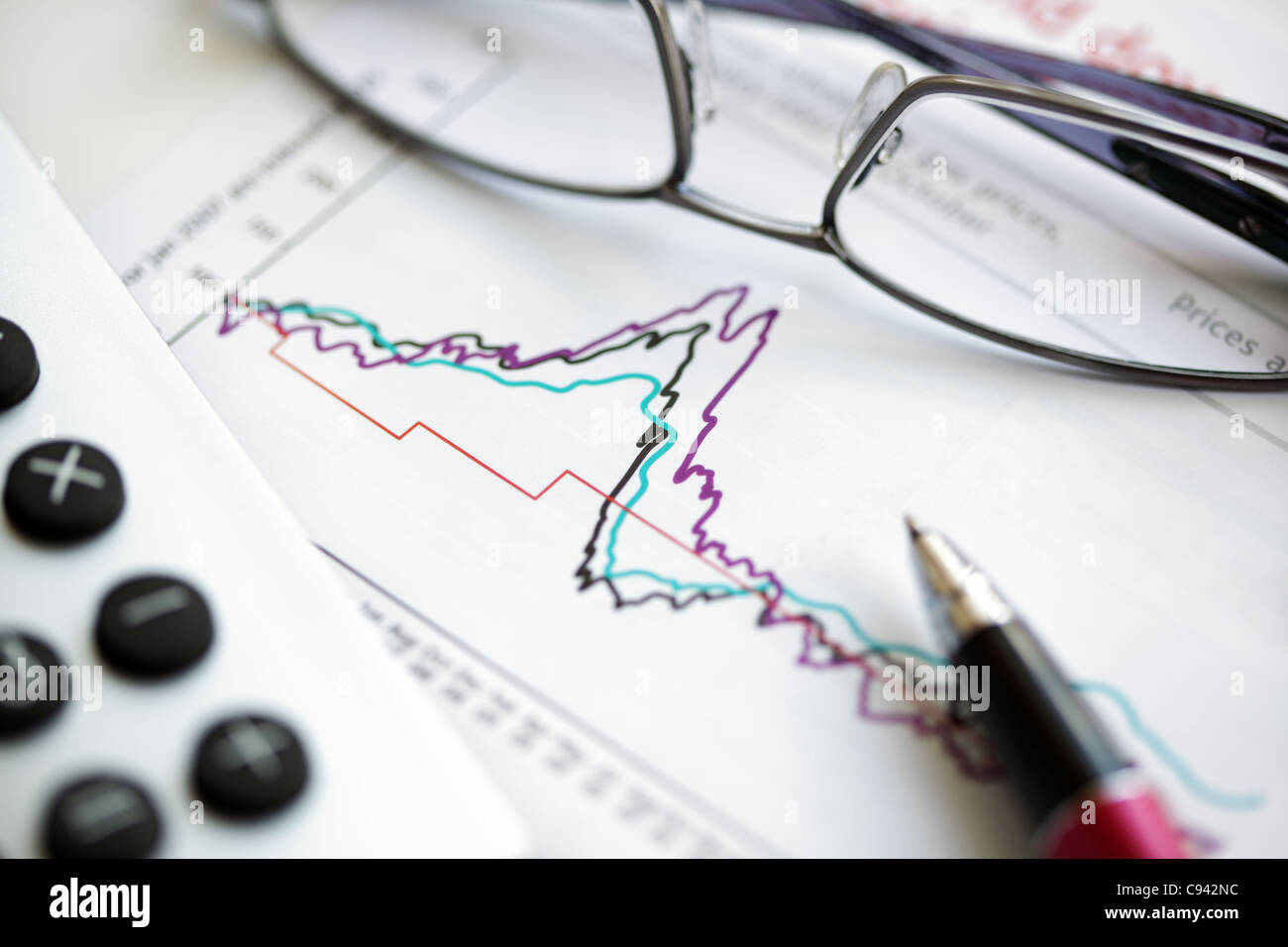 Pen glasses and calculator on stock chart - Stock Image