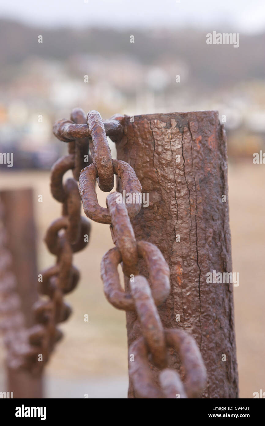 Close up view of rusty chain links and fence post. Focus on top chain link and blurred background. - Stock Image