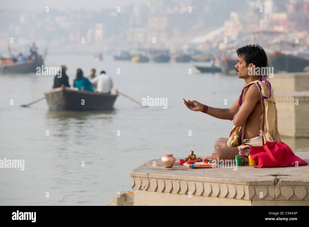 Sadhu praying on the ghats lining the River Ganges, with a rowboat in the background, Varanasi, Uttar Pradesh, India - Stock Image