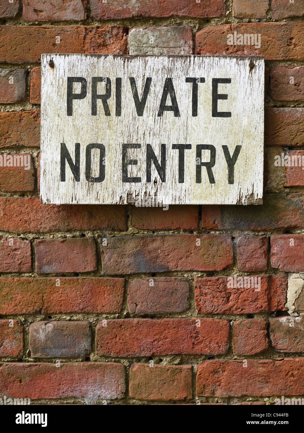 Decaying Private, No Entry sign fixed to weathered brick wall. Vertical format, sign located in top half of frame. - Stock Image
