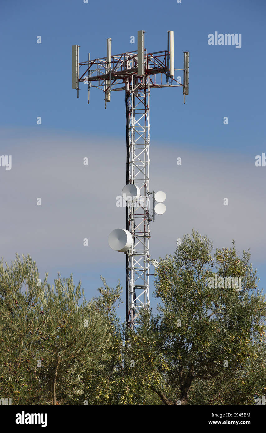 Phone antenna located among trees with a blue sky background - Stock Image