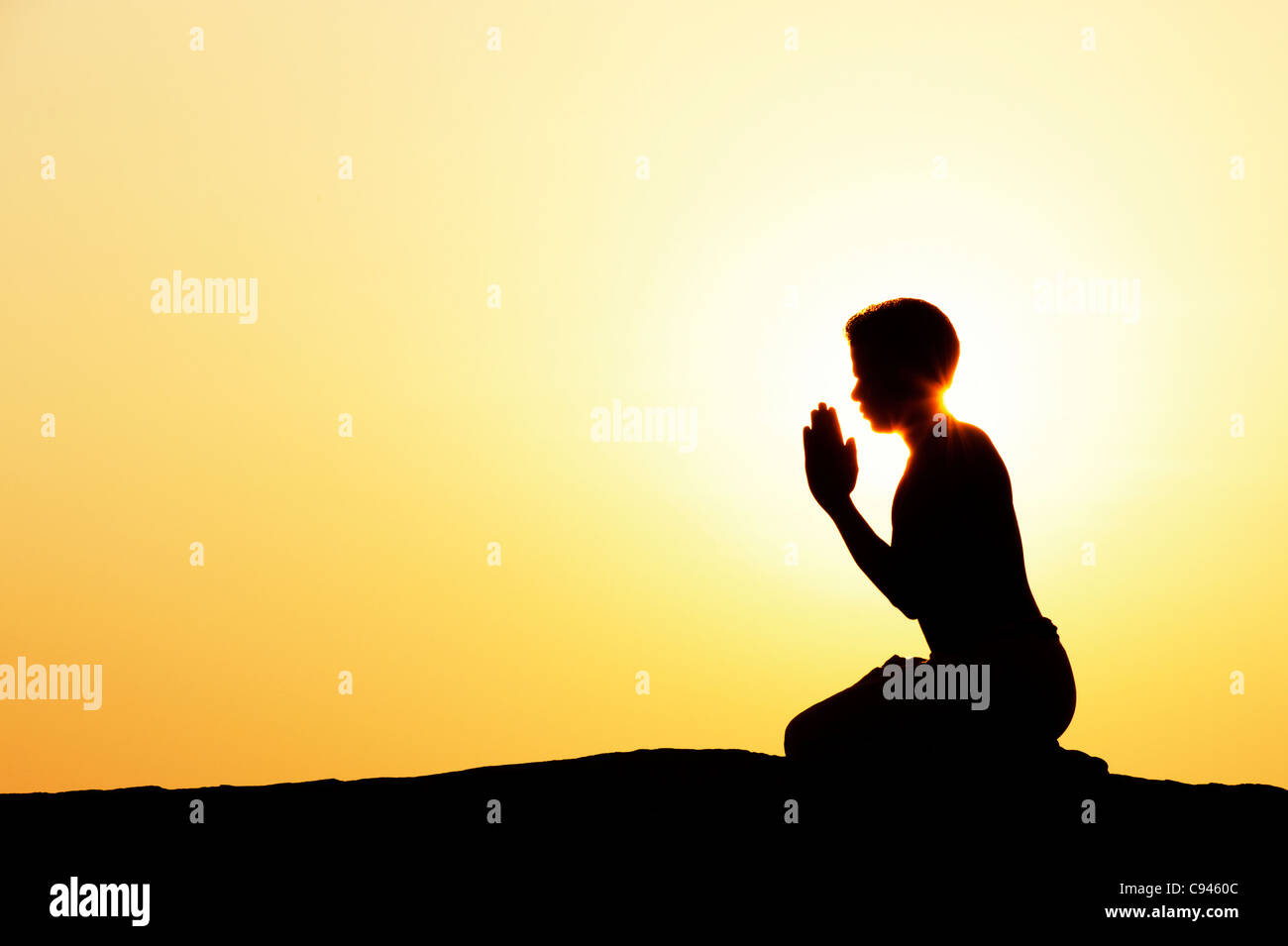 Indian man offering prayers to the sun at sunset. Silhouette. India - Stock Image