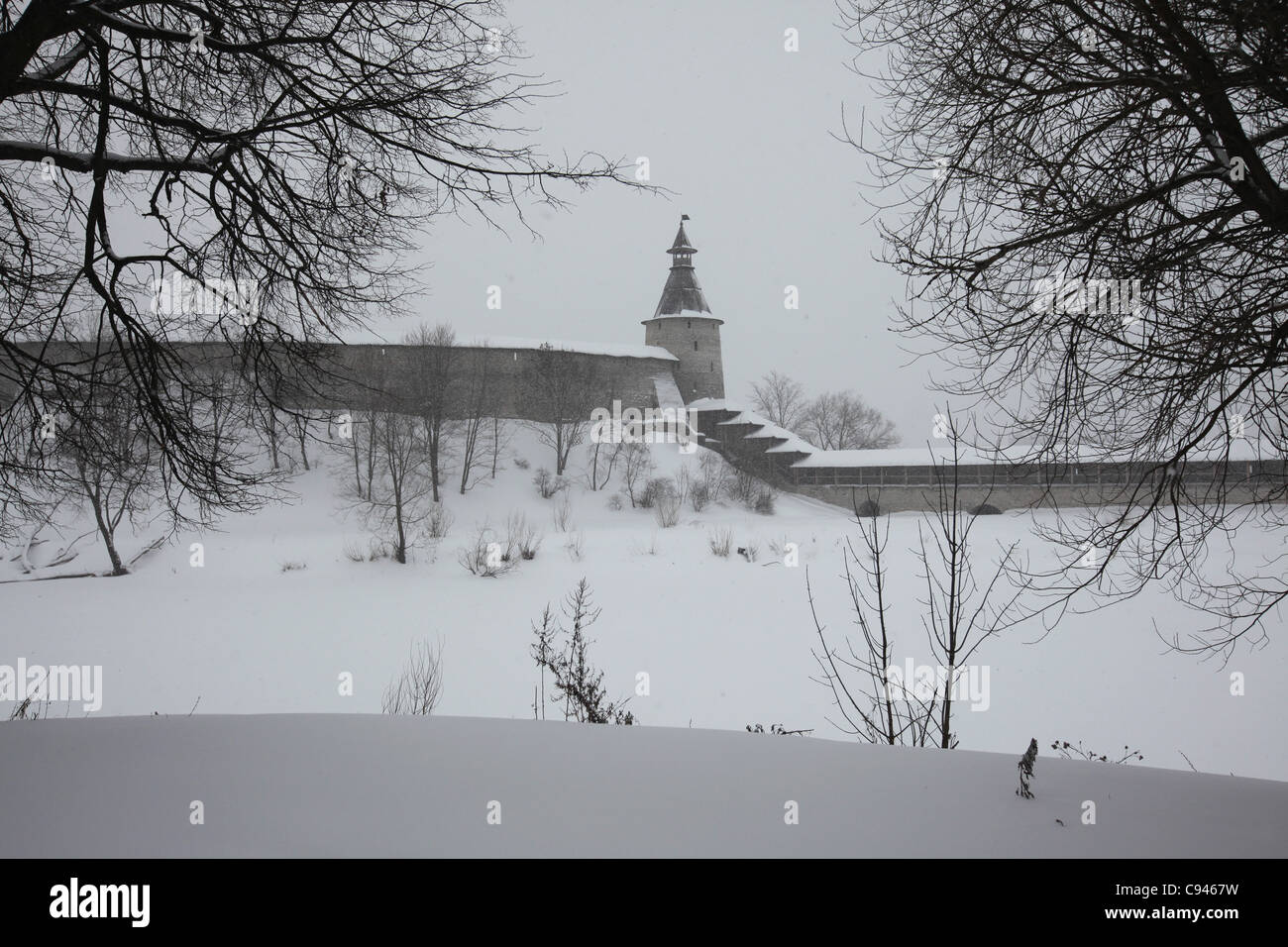 Kutekroma Tower of the Pskov Kremlin in Pskov, Russia. The Pskova River under ice is seen in the foreground. - Stock Image