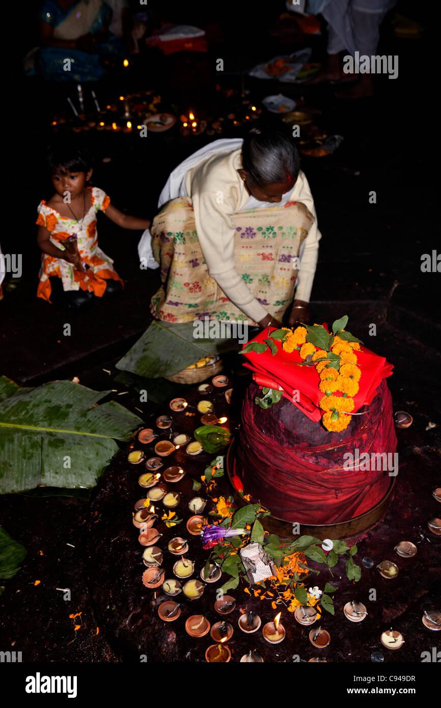 India, Assam, Guwahati, Navagraha Hill, Nabahraha Mandir, worshipper at red wrapped planetary shivalingam - Stock Image