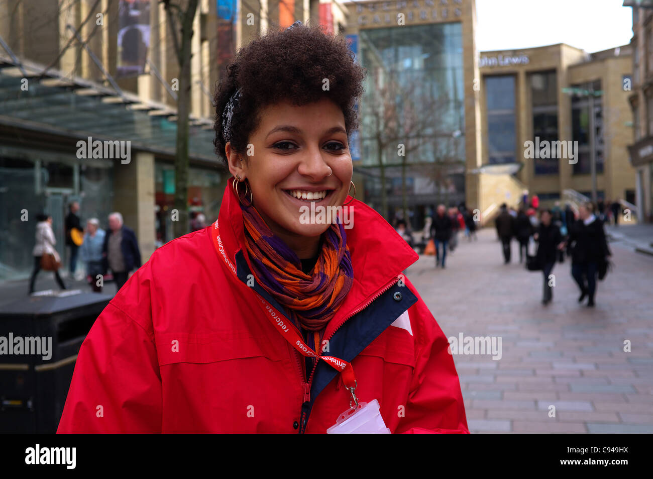 Young woman acting as a Street canvasser for the British Red Cross Charity in Sauchiehall Street, Glasgow - Stock Image