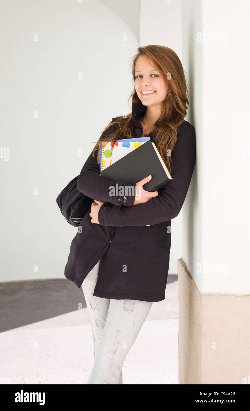 Portrait of a pretty young student girl outdoors in black jacket and jeans.  - Stock