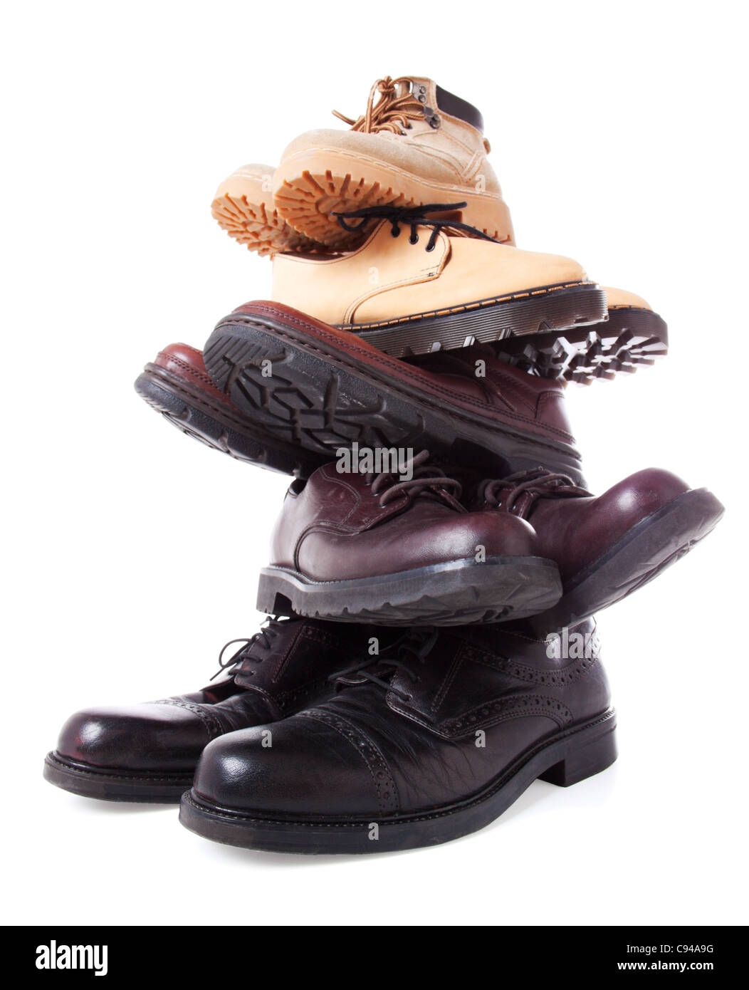 Stack of male leather boots isolated over white background. Low point of view. Wide angle shot - Stock Image