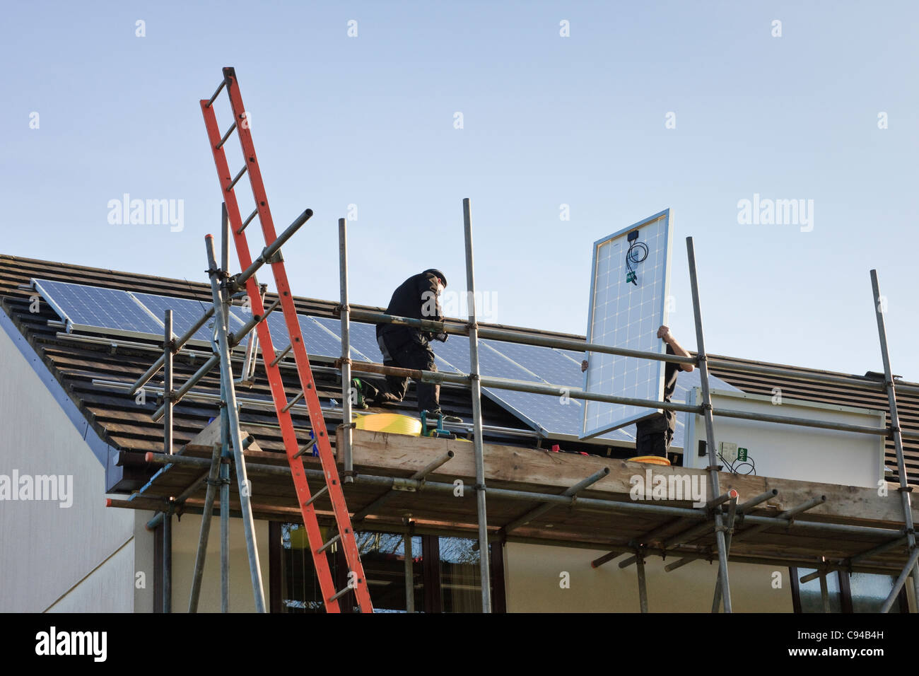 UK, Britain. Workmen fitting new solar panels to a house roof for the Feed-in Tariff scheme - Stock Image