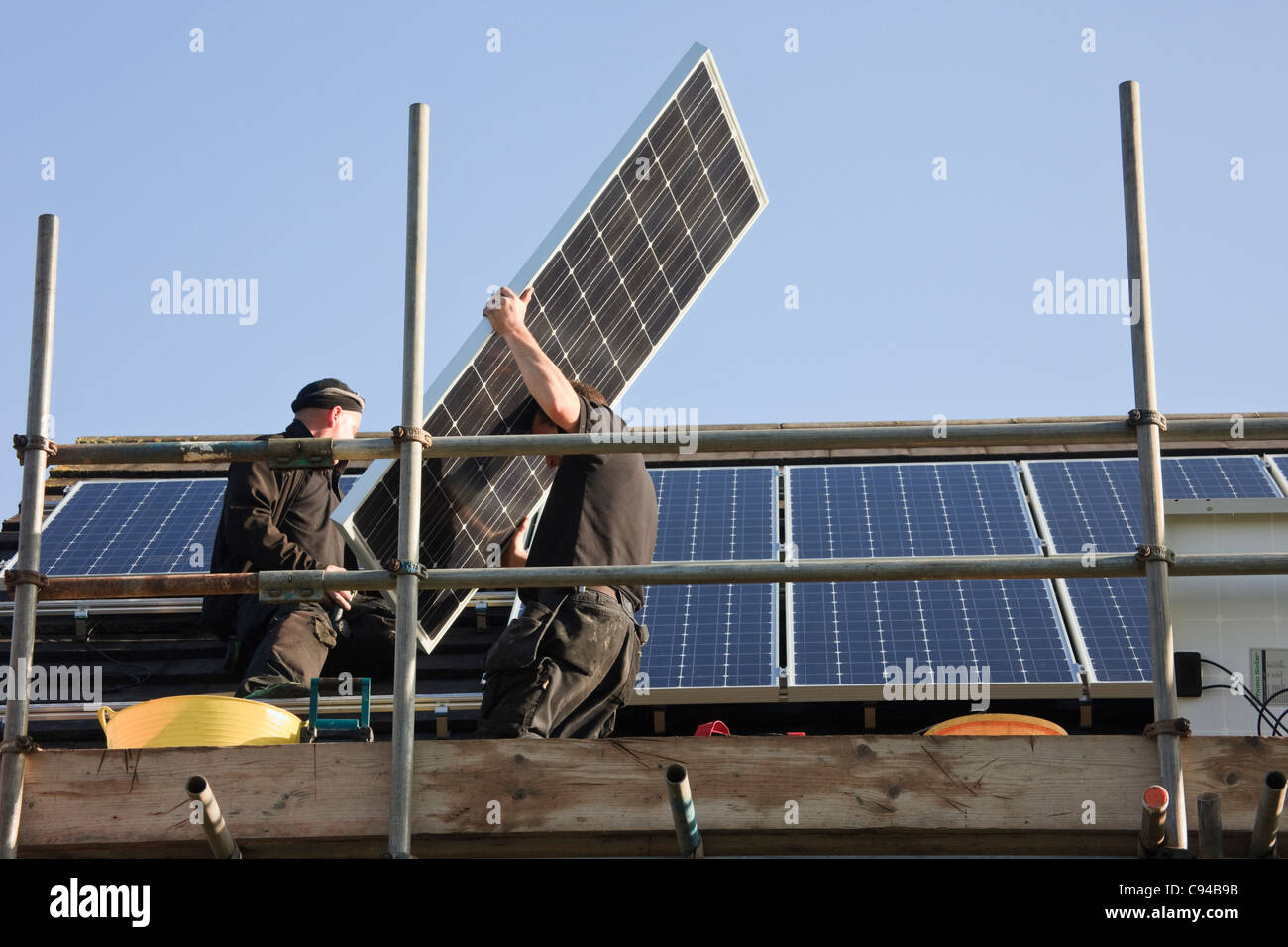 UK, Britain, Europe. Workmen fitting new solar panels to a house roof for the Feed-in Tariff scheme - Stock Image