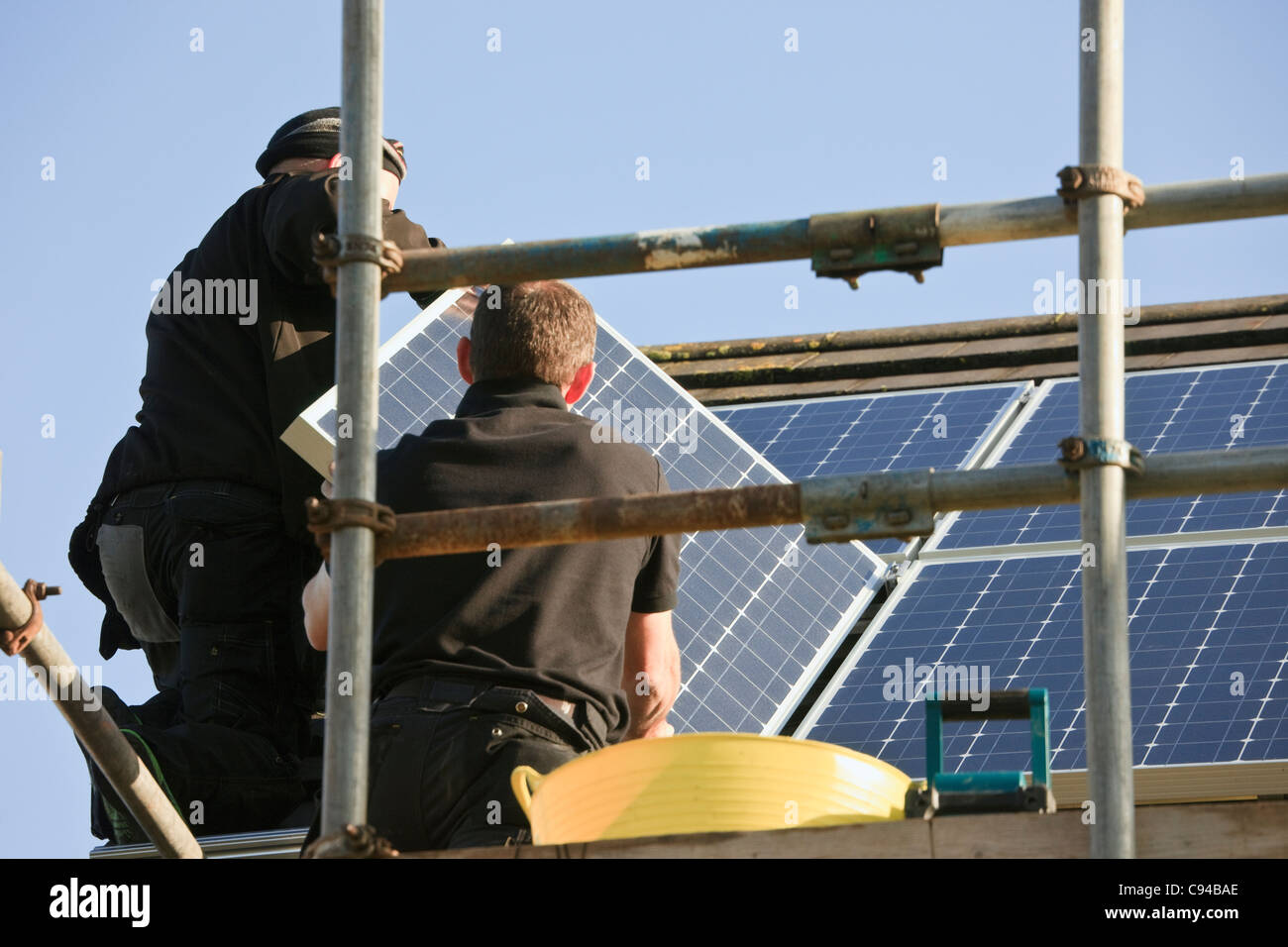 UK, Britain, Europe. Workmen installing new solar panels to a house roof for the Feed-in Tariff scheme - Stock Image