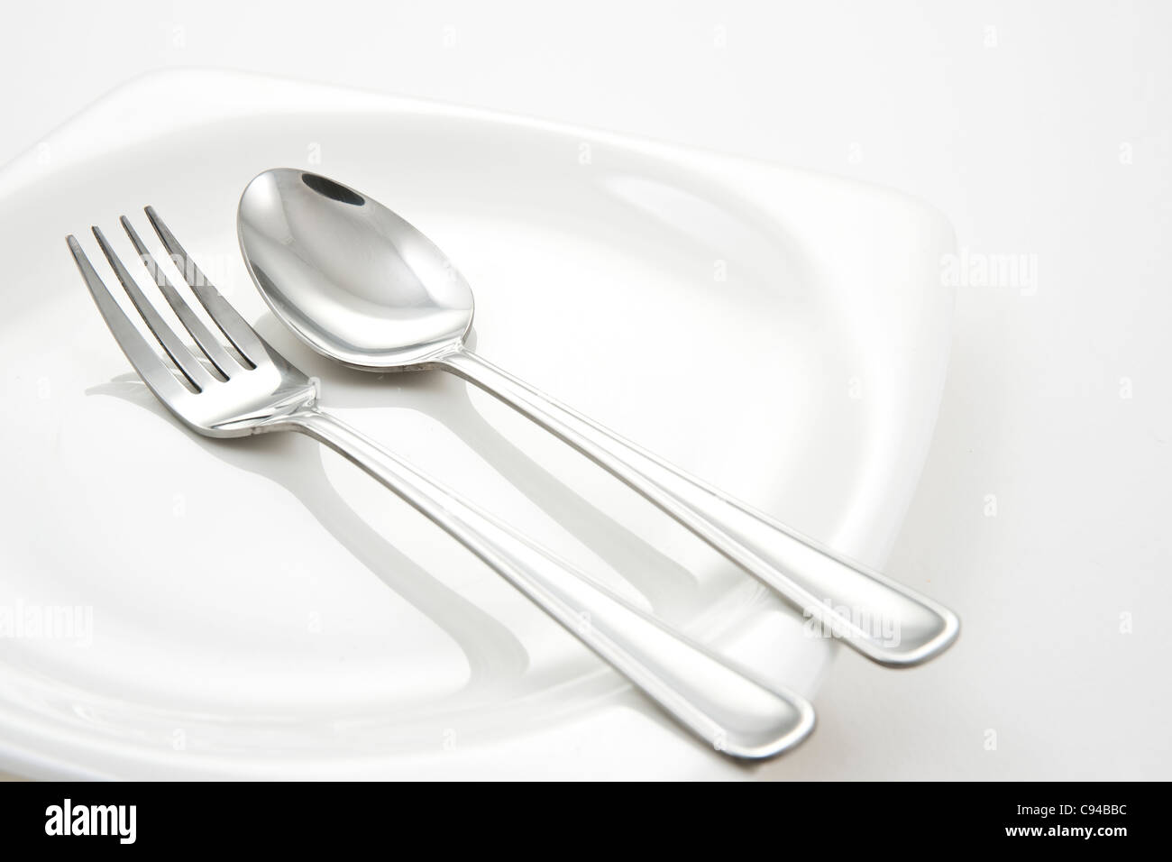 Fork and Spoon on white plate - Stock Image