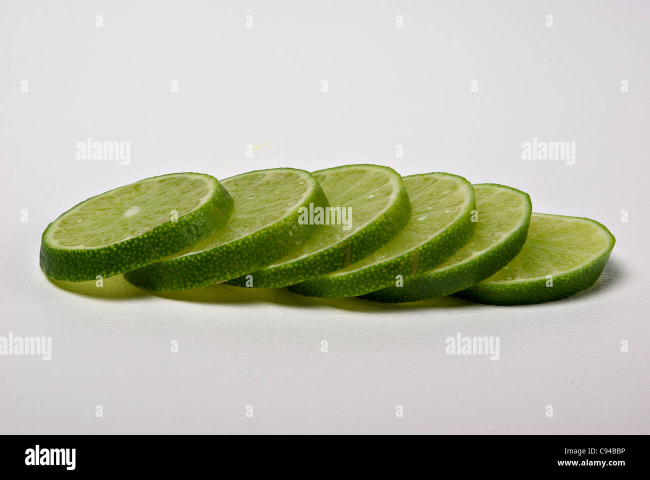 Lime slices lay on a plain background. - Stock Image