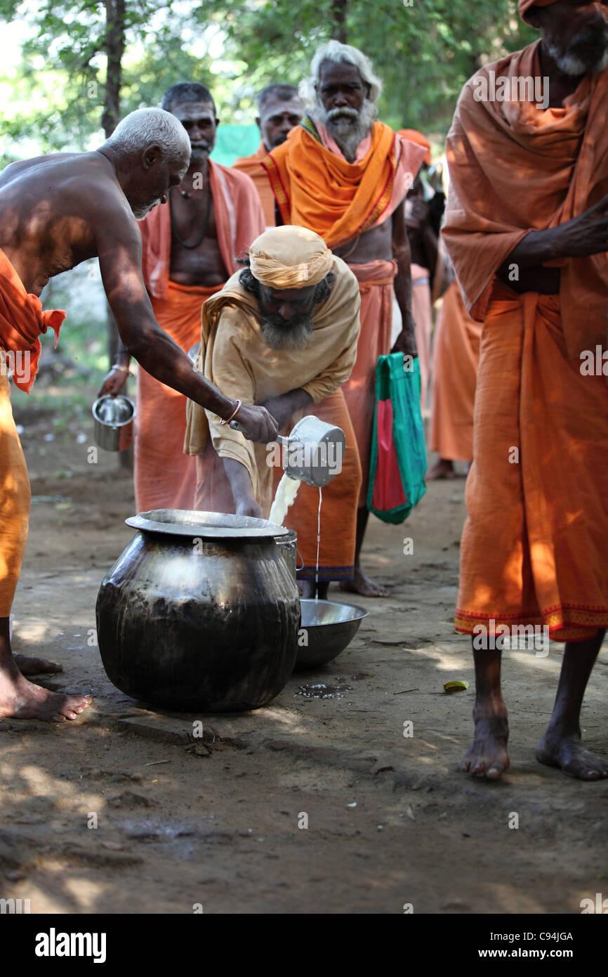 Men sadhu receiving free food Arunachala South India - Stock Image