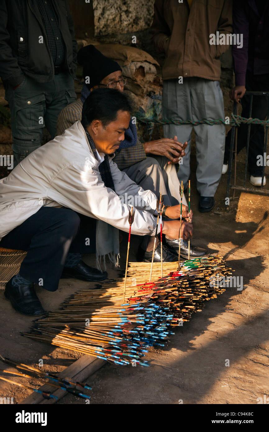 India, Meghalaya, Shillong, Bola archery gambling game, officials sorting and counting number of arrows - Stock Image