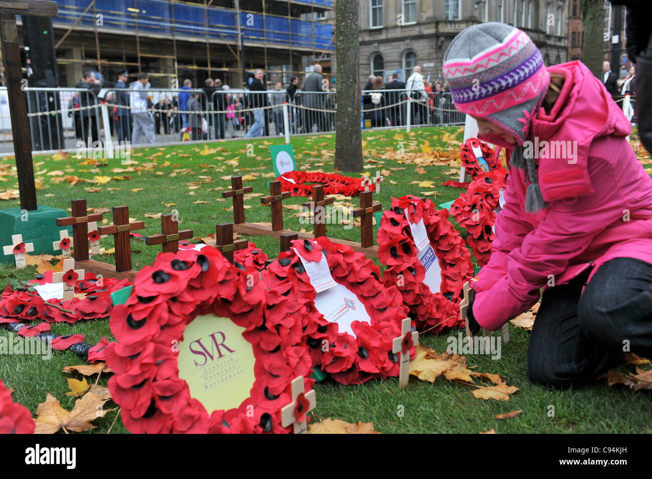 A young girl plants a cross with a poppy on it in Glasgow's Garden of Remembrance during Armistice Day commemoration. - Stock Image