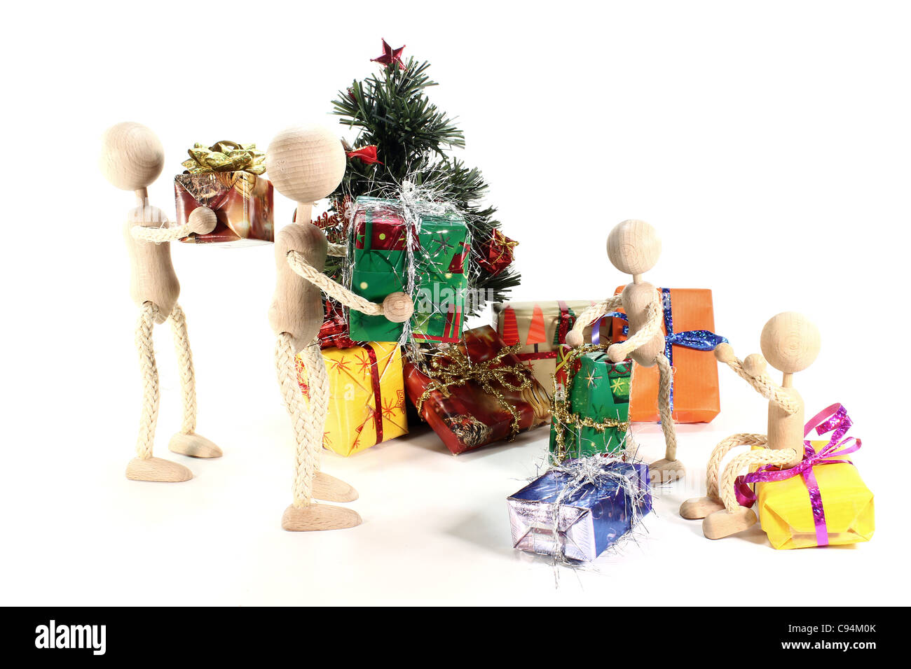 Wooden Dolls in the nice mess and Christmas tree with colorful gifts - Stock Image