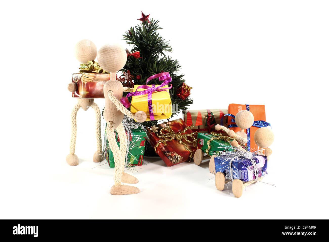Wooden figures at the presents and Christmas tree with gifts - Stock Image