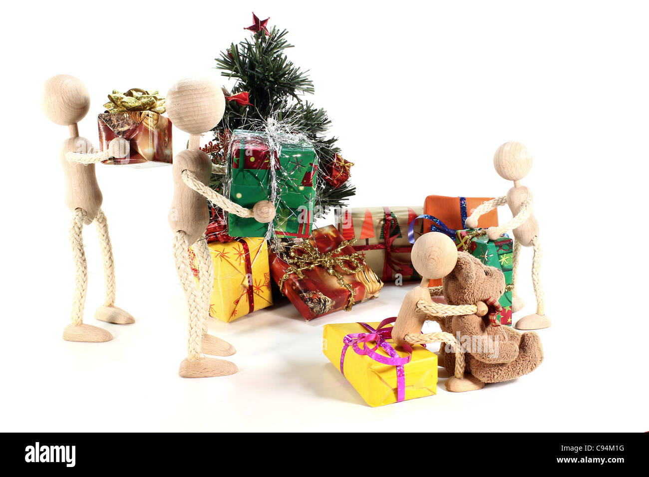 Figures at the handing out of presents and Christmas tree with many gifts - Stock Image
