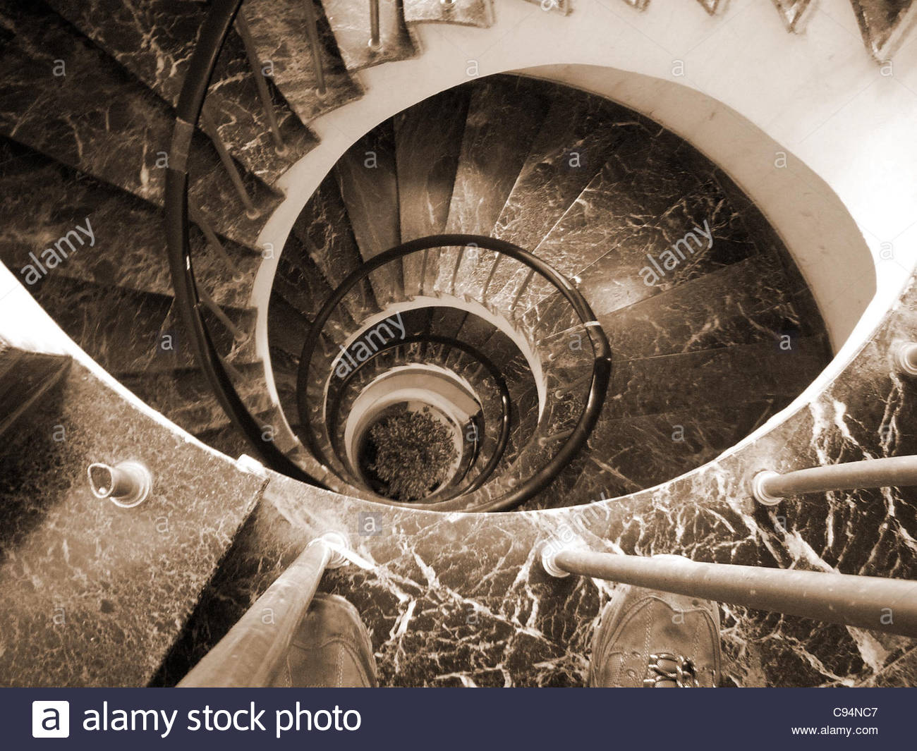 Sepia black and white monochrome Spiral staircase aerial stairs descending down steps - Stock Image