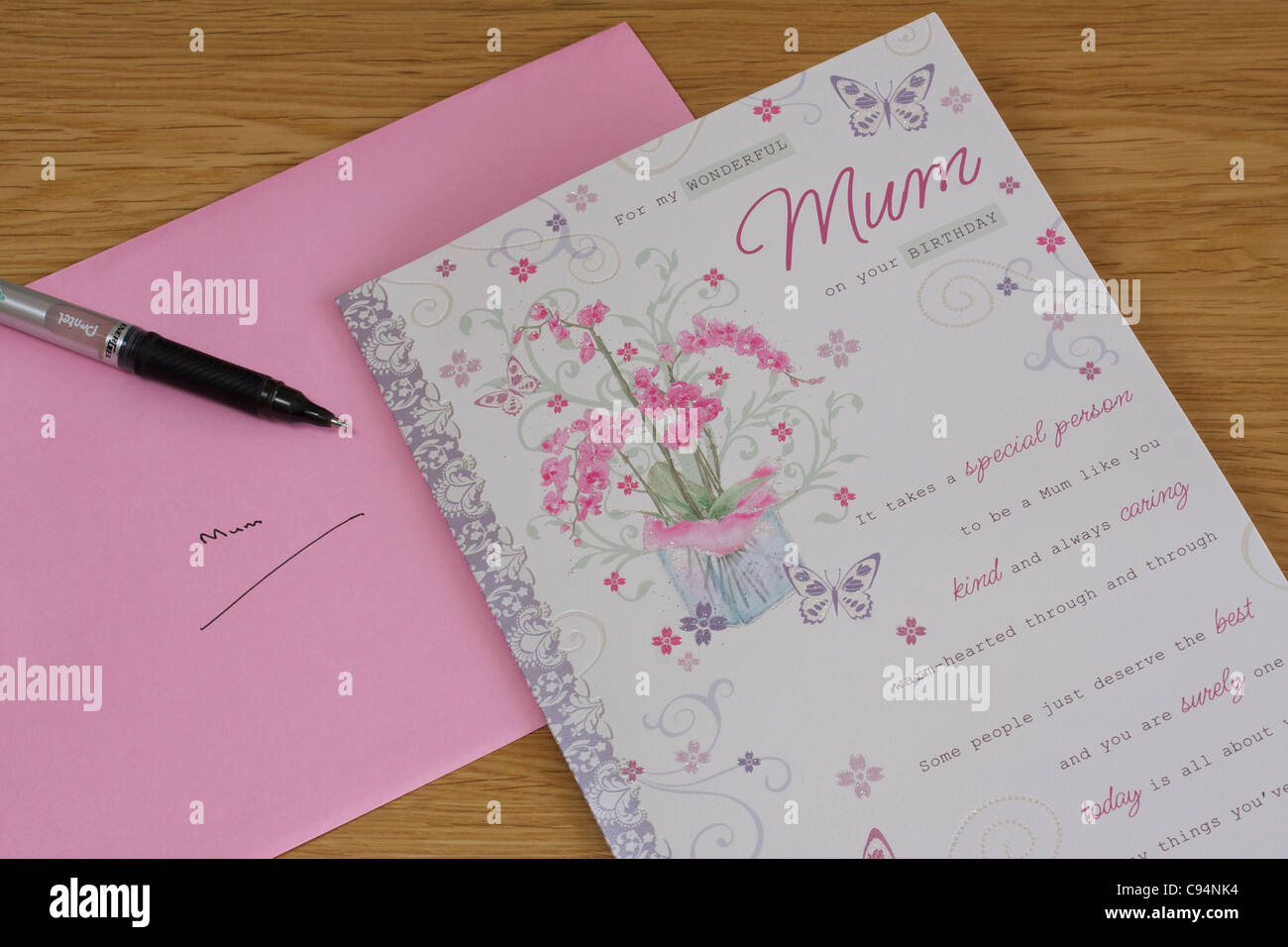 birthday card pen and pink envelope against wooden table background