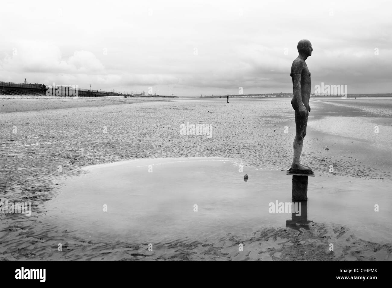 Antony Gormley's Another Place, Waterloo beach, Crosby, Merseyside, UK - Stock Image