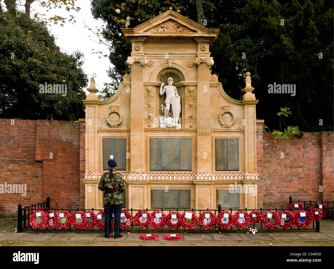 Lone soldier with wreaths of poppies in Lichfield Memorial Gardens on Remembrance Sunday 2011 - Stock Image
