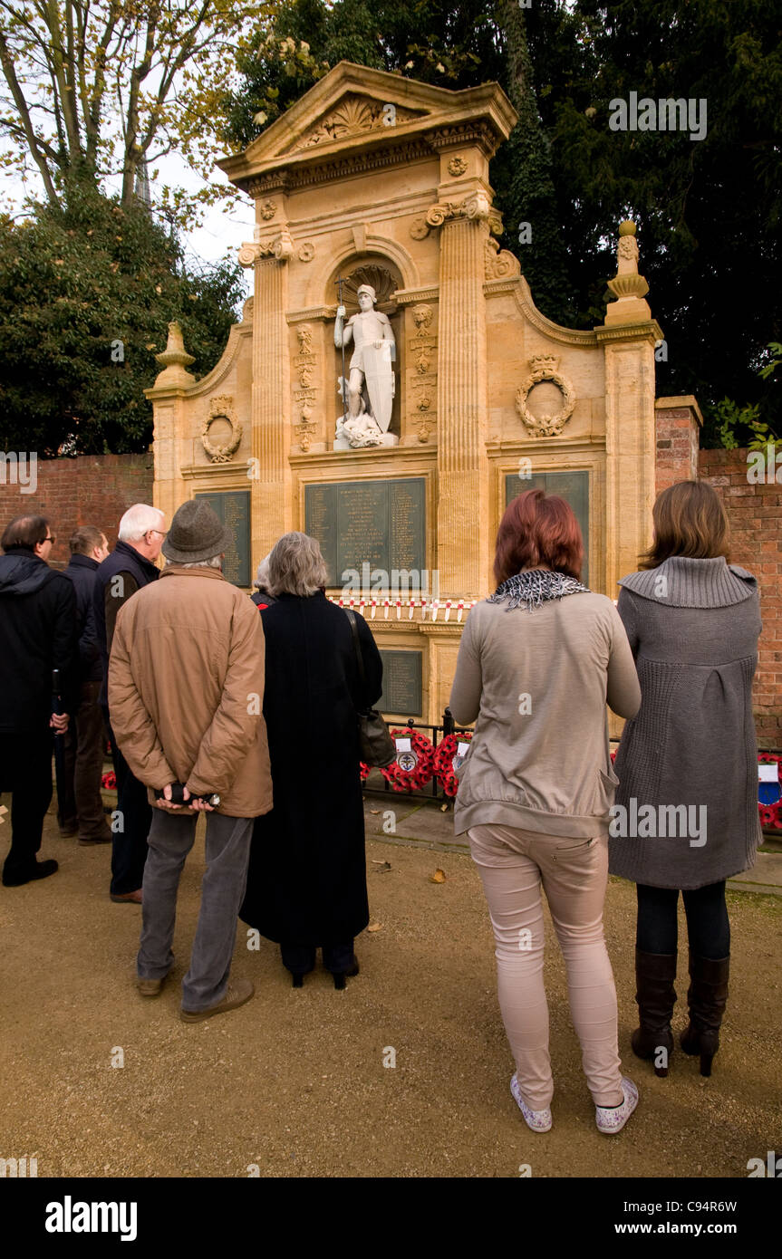 People take a quiet moment to look at wreaths and poppies after Remembrance Day Service in Lichfield Staffordshire - Stock Image