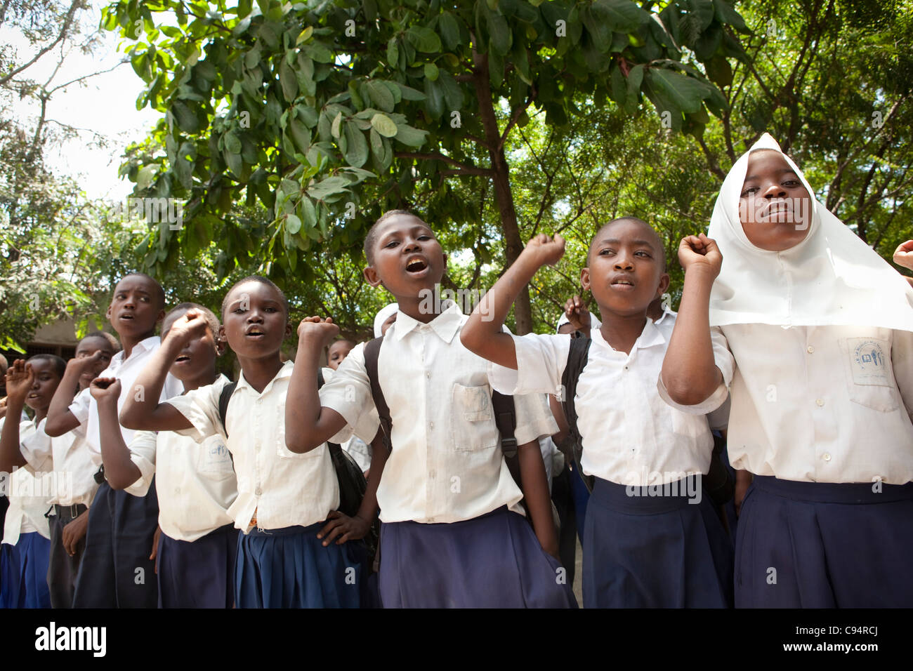A group of students sings in assembly at a primary school in Dar es Salaam, Tanzania, East Africa. - Stock Image