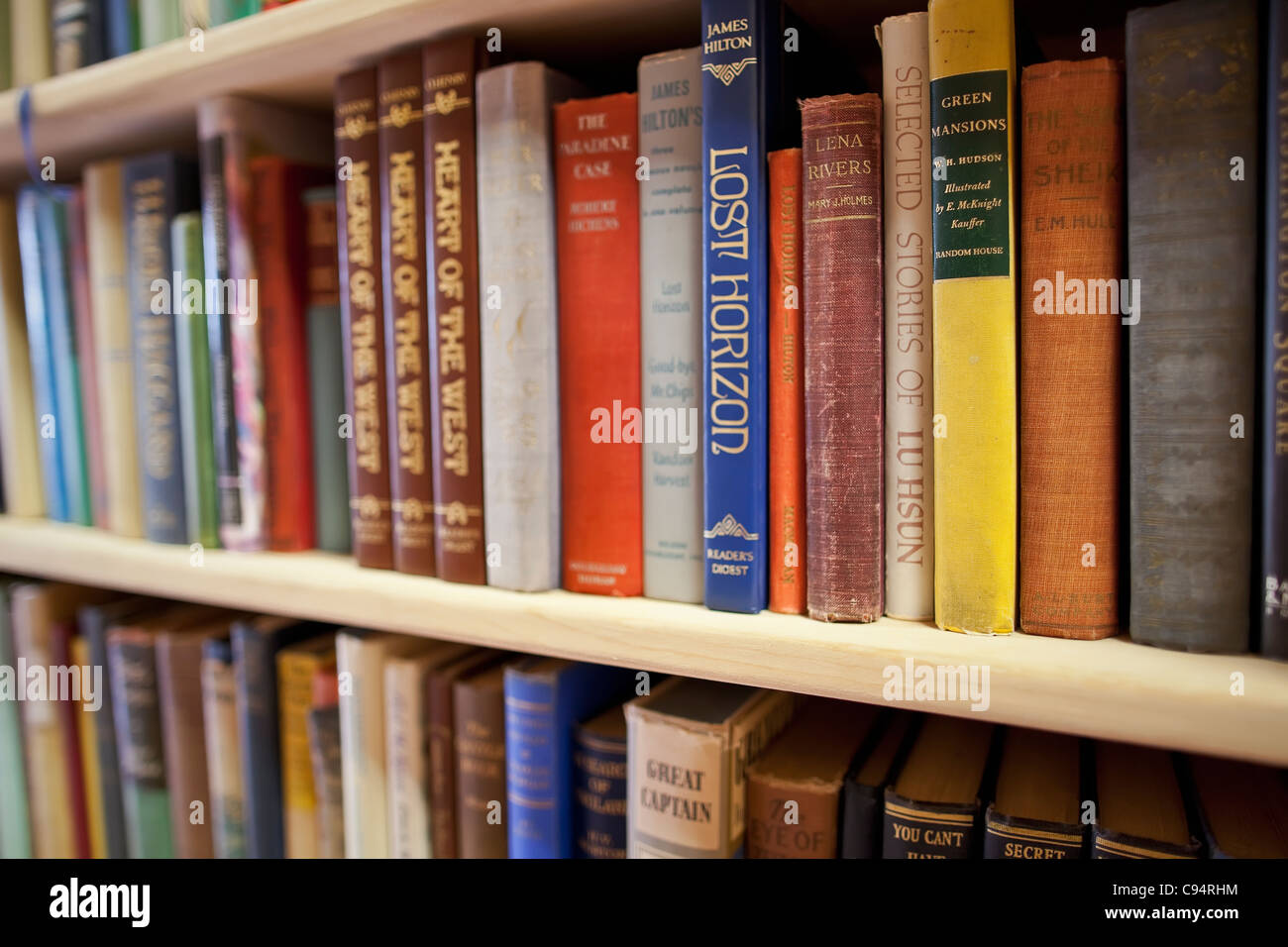 Hardcover books on shelves at a used bookstore. - Stock Image