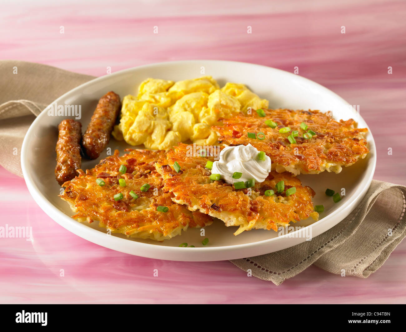 Potato pancake breakfast topped with sour cream and served with scrambled eggs and sausage - Stock Image