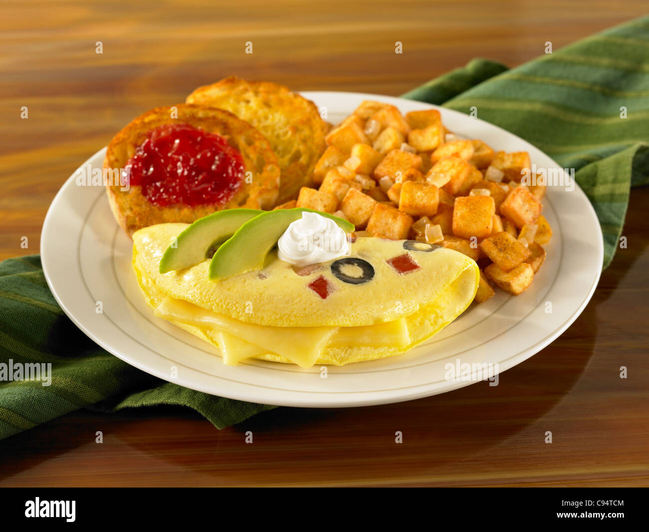 A cheese omelet topped with sour cream and avocado slices served with potato and english muffin with jelly - Stock Image