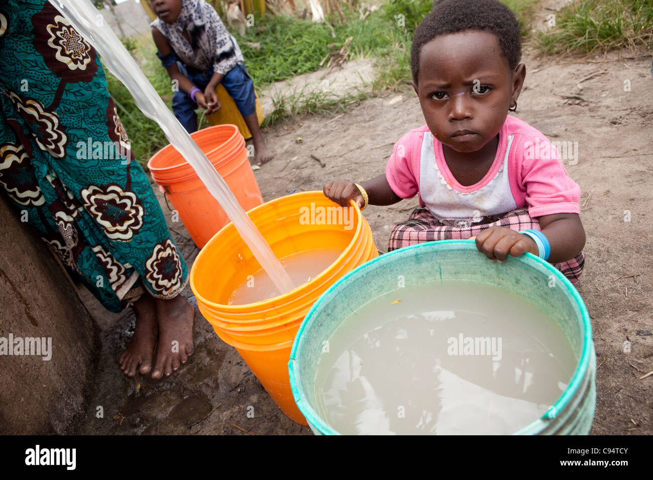 A child sits with dirty water at a well outside Dar es Salaam, Tanzania, East Africa. - Stock Image