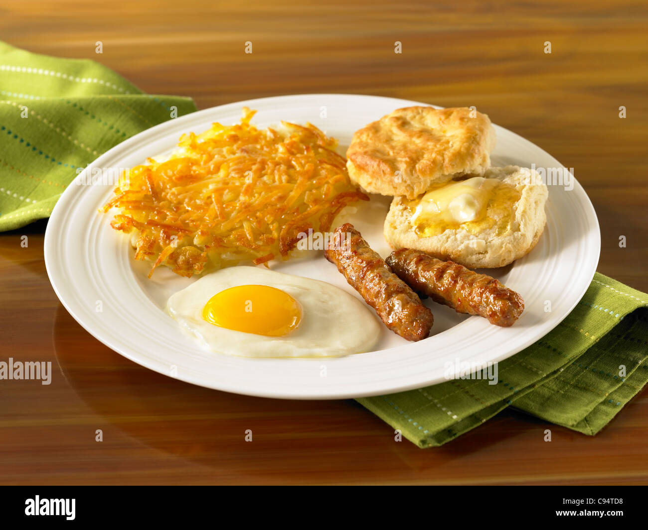Egg breakfast with hash browns, sausage and biscuits with butter - Stock Image